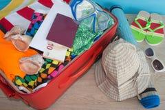 Превидение рейса Одежды и аксессуары ` s женщин в красном чемодане Стоковое Изображение
