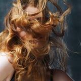 Превосходное вьющиеся волосы Счастливая красивая redheaded девушка Портрет студии на текстурированной предпосылке Длинные волосы  Стоковое Изображение