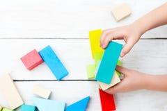 Превращаясь деревянные игрушки Руки ребенка и деревянных кубов на w Стоковое Изображение RF