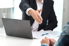 Предложение бизнесмена и дает руку для рукопожатия в офисе Стоковая Фотография RF