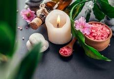 Предметы первой необходимости курорта включая свечу, соль, камни, масло и листья зеленого цвета Стоковое Изображение