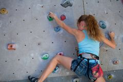 Предназначенная для подростков девушка взбираясь стена утеса крытая Стоковые Фото