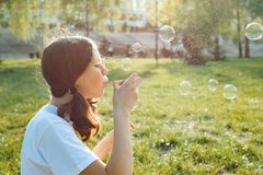 Предназначенная для подростков девушка имея потеху в парке - дуя пузыри мыла, золотой час стоковые изображения