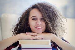 Предназначенная для подростков девушка отдыхая на книгах Стоковая Фотография
