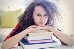 Предназначенная для подростков девушка отдыхая на книгах Стоковое Фото
