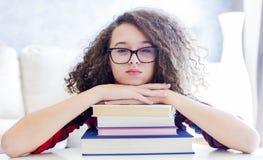 Предназначенная для подростков девушка отдыхая на книгах Стоковые Изображения RF