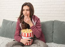 Предназначенная для подростков девушка сидя на кресле с ТВ удаленным и есть попкорн стоковые изображения