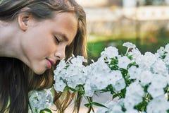 Предназначенная для подростков девушка с цветками длинных волос пахнуть белыми outdoors в летнем дне стоковые фотографии rf