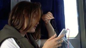 Предназначенная для подростков девушка с smartphone на поезде видеоматериал