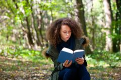 Предназначенная для подростков книга чтения девушки в парке осени Стоковое фото RF