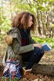 Предназначенная для подростков книга чтения девушки в парке осени Стоковая Фотография RF