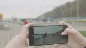 Предназначенное для подростков видео стрельбы мальчика катаясь на коньках друга по телефону сток-видео