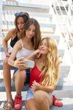 Предназначенные для подростков девушки лучших другов в ряд с smartphone Стоковое Фото