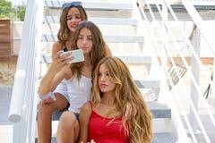 Предназначенные для подростков девушки лучших другов в ряд с smartphone Стоковые Изображения RF