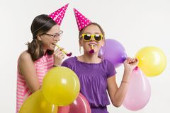 Предназначенные для подростков девушки на партии Девушки на белой предпосылке, в праздничных шляпах, дуя в трубах Стоковые Фото