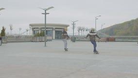 Предназначенные для подростков конькобежцы шагая и свертывая на скейтбордах