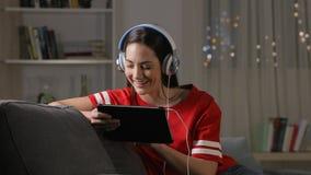 Предназначенные для подростков наблюдая и слушая средства массовой информации на планшете в ночи видеоматериал