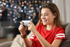 Предназначенные для подростков наблюдая средства массовой информации в умном телефоне в ноче стоковые изображения