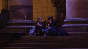 Предназначенные для подростков пары используя smartphone на ноче видеоматериал