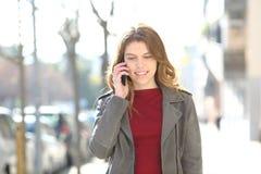 Предназначенные для подростков прогулки говоря по умному телефону в улице стоковые изображения