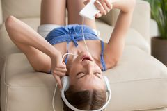 Предназначенный для подростков в наушниках лежа на софе, наслаждаясь музыкой на телефоне Стоковая Фотография RF