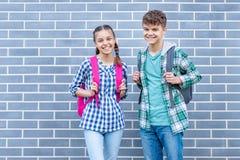 Предназначенный для подростков мальчик и девушка назад в школу стоковые изображения