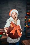 Предназначенный для подростков мальчик нося шляпу Санта держа большой шарик рождества в темной комнате с украшенной деревянной ле стоковое изображение rf