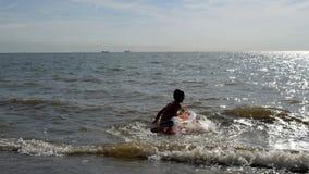 Предназначенный для подростков мальчик плавает на великобританское взморье на раздувном тюфяке акции видеоматериалы