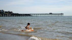 Предназначенный для подростков мальчик плавает на великобританское взморье на раздувном тюфяке сток-видео
