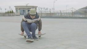 Предназначенный для подростков мальчик связывая шнурки сидя на скейтборде