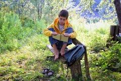 Предназначенный для подростков мальчик читая книгу стоковое фото