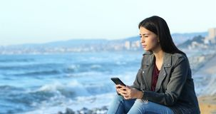 Предназначенный для подростков проверяя телефон и смотреть горизонт на пляже сток-видео