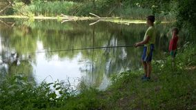 Предназначенный для подростков ребенок улавливает рыболовную удочку на пруде сток-видео
