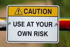 Предосторежение использует на свой страх и риск знак стоковое изображение rf