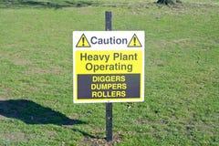 Предосторежение - тяжелый завод работая - ролики Dumpers землекопов подписывает - предупреждающ для людей стоковые изображения
