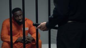 Предохранитель тюрьмы с жезлом смотря афро-американского пленника в клетке, домогательстве сток-видео