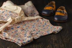 Предпосылка аксессуаров младенца: светлые платье и ботинки цветка для ба Стоковые Изображения