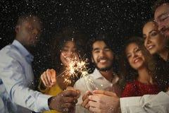Предпосылка бенгальских огней Молодые люди на партии торжества стоковое изображение