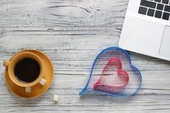 Предпосылка валентинки на деревянном столе с чашкой компьтер-книжки  Стоковые Изображения