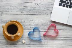 Предпосылка валентинки на деревянном столе с чашкой компьтер-книжки  Стоковые Фото