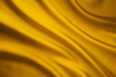Предпосылка волны Silk ткани, желтая текстура ткани сатинировки стоковое фото rf