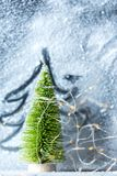 Предпосылка времени рождества - покрытое Снег окно с зелеными, символическими деревом и светами стоковые фото