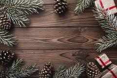 предпосылка всходя на борт древесины коричневой части крытой Ветви ели, декоративные конусы ели Подарки для xmas Поздравительная  Стоковое фото RF