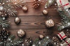 предпосылка всходя на борт древесины коричневой части крытой Ветви ели, конусы ели и декоративные грецкие орехи Подарки для xmas  Стоковые Изображения RF