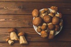 Предпосылка гриба, взгляд сверху грибов в плите на деревянном столе стоковая фотография rf