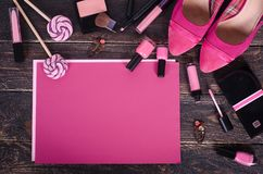 Предпосылка дам - тюльпаны, ботинки, губная помада, маникюр, серьги, краснеет, леденцы на палочке на розовой бумаге и деревянная  стоковое фото