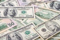 Предпосылка дела абстрактная - банкноты конца-вверх долларов, разбросанные на плоскую поверхность Стоковые Изображения