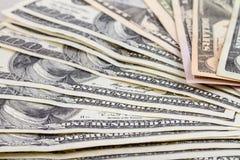 Предпосылка дела абстрактная - банкноты конца-вверх долларов, разбросанное похожего на вентилятор на плоской поверхности стоковое изображение