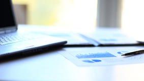 Предпосылка дела: финансовые статистик, тетрадь и ручка на рабочем месте офиса Стоковое Изображение