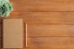 Предпосылка деревянного стола стола офиса с насмешкой вверх по тетрадям и карандашу и заводу Стоковые Фотографии RF